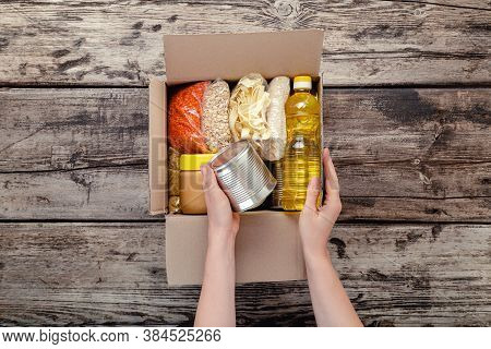 Female Hands Packing Donation Box With Food Items Of Staple Products On Wooden Table. Person Woman R