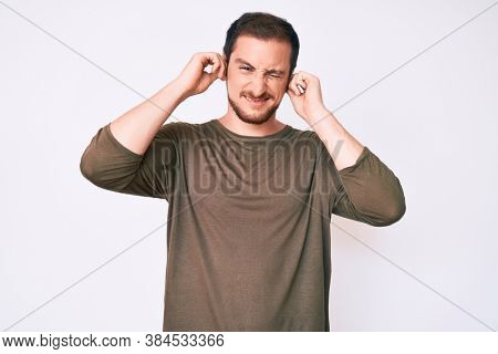 Young handsome man wearing casual clothes covering ears with fingers with annoyed expression for the noise of loud music. deaf concept.