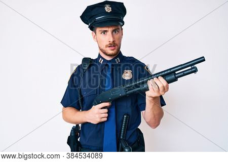 Young caucasian man wearing police uniform holding shotgun in shock face, looking skeptical and sarcastic, surprised with open mouth