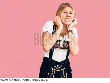Young beautiful blonde woman wearing oktoberfest dress covering ears with fingers with annoyed expression for the noise of loud music. deaf concept.