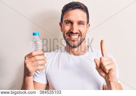 Young handsome man drinking bottle of water to refreshment over isolated white background smiling with an idea or question pointing finger with happy face, number one