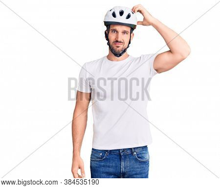 Young handsome man wearing bike helmet confuse and wonder about question. uncertain with doubt, thinking with hand on head. pensive concept.
