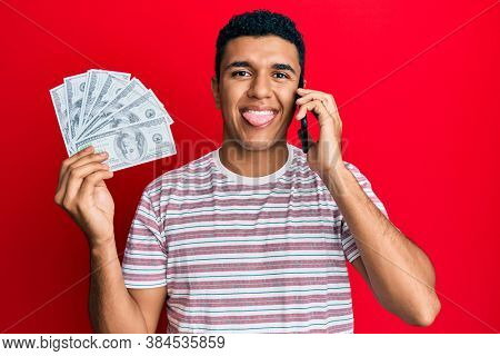 Young arab man having conversation talking on the smartphone holding dollars sticking tongue out happy with funny expression.
