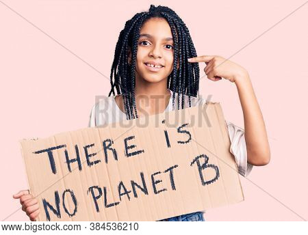 Cute african american girl holding there is no planet b banner pointing finger to one self smiling happy and proud