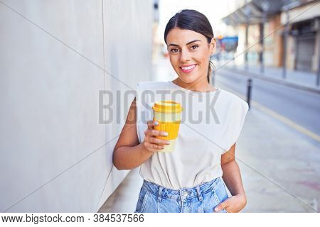 Beautiful young woman wearing fashionable clothes walking down the street drinking a take away cup of coffee