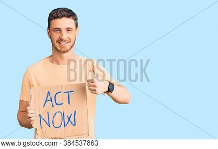 Handsome young man with bear holding act now banner smiling happy and positive, thumb up doing excellent and approval sign