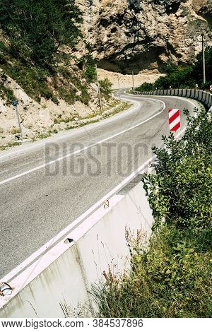 Curvy Road With Traffic Signs In Mountains. Red Diagonal Keep Left Obstacle Traffic Sign Placed On S