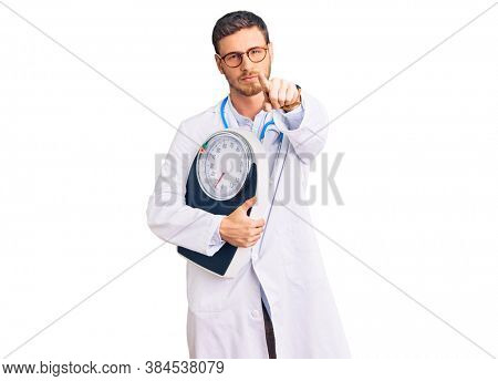 Handsome young man with bear as nutritionist doctor holding weighing machine pointing with finger to the camera and to you, confident gesture looking serious