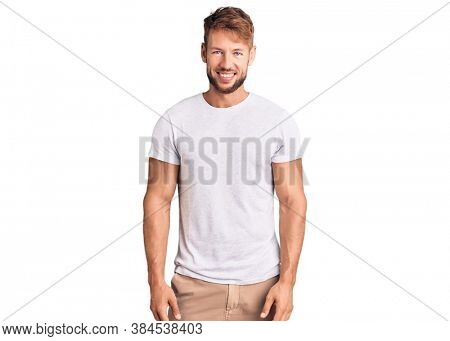 Young caucasian man wearing casual white tshirt with a happy and cool smile on face. lucky person.