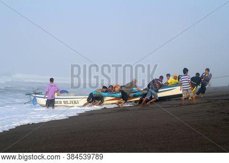 Yogyakarta, Indonesia - September 20, 2016: Some People Help Pull Fishing Boats To The Beach Of Goa