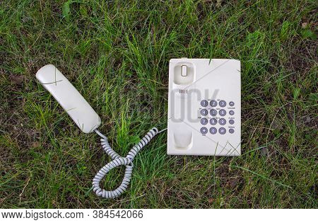 Communication With The Earth. Allegory. A Telephone With A Receiver Is Located On A Green Lawn. Enco