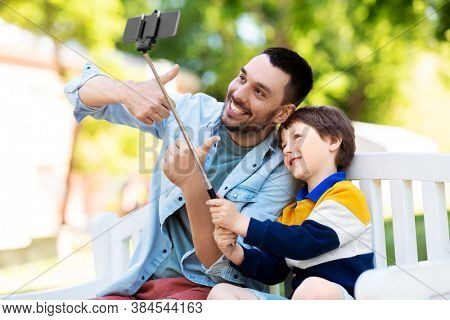 family, fatherhood and people concept - happy father and his little son taking picture with smartphone and selfie stick and showing thumbs up at summer park