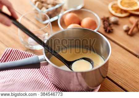 christmas and seasonal drinks concept - pot with eggnog and ladle, glass, ingredients and aromatic spices on wooden table
