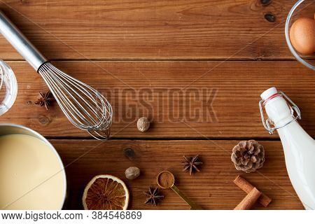 christmas and seasonal drinks concept - pot with eggnog, ingredients and aromatic spices on wooden background
