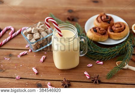 christmas and seasonal drinks concept - eggnog in glass mug with candy cane decoration, cinnamon buns, fir tree brunch and aromatic spices on wooden background