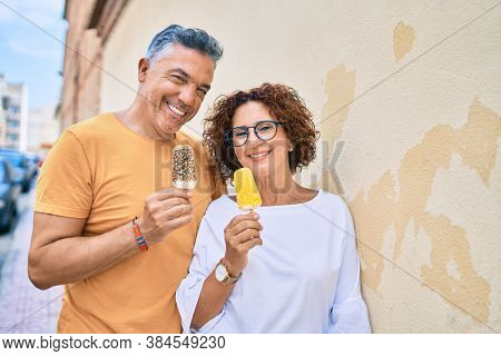 Middle age couple smiling happy eating ice cream leaning on the wall at street of city.