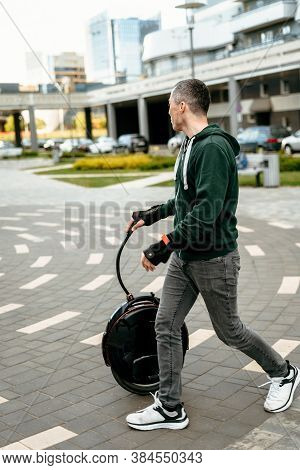Man Transports Aunicycle On Street, Electric Unicycle Close Up.