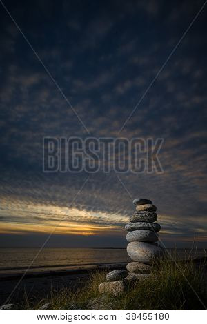 Pebble sculpture on a beach. with an evening sky and gentle sunset. poster