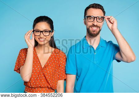 Young Interracial Couple Looking At Camera While Touching Eyeglasses Isolated On Blue