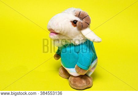 Toy Plush Soft Lamb Ram Sheep In Clothes On A Yellow Background. Baa-lamb.