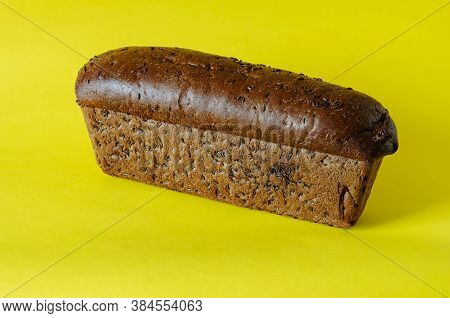 Loaf Of Rye Bread With Caraway Seeds On A Yellow Background. Side View Of Freshly Baked Homemade Bre
