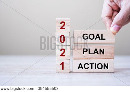 Businessman Hand Holding Wooden Cube With Text 2021 Goal, Plan And Action On Table Background. Resol