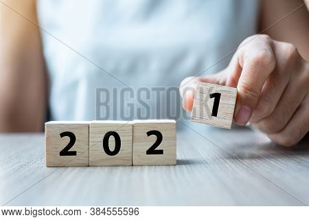 Business Woman Hand Holding Wooden Cube With 2021 Word On Table Background. Resolution, Strategy, So