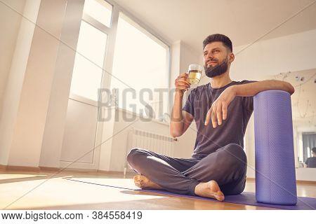 Bearded Young Man Drinking Herbal Tea In Yoga Studio
