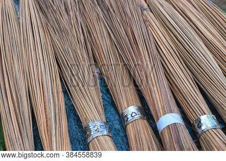 Wooden Rods Bunch. Rustic Broom For Sale On Market Table. Natural Material For Household Broom. Rust