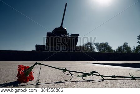 memorial to the fallen soldiers in world war II, T34 tank on a pedestal and one broken red carnation flower, a tribute and tragic