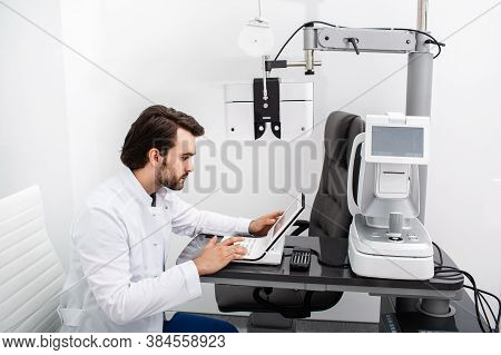 Experienced Optometrist Sitting At His Workplace In A Modern Ophthalmology Clinic. Vision Test And V