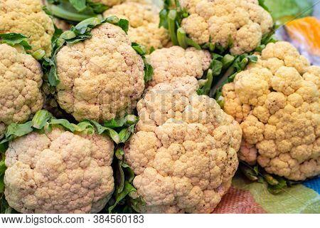 Ripe White Cauliflower Pile Closeup Photo. White And Green Cabbage Pile On Farmer Market Table. Fres