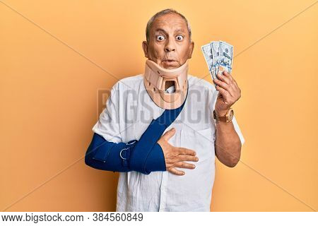 Handsome mature injured man wearing cervical collar and sling holding insurance money in shock face, looking skeptical and sarcastic, surprised with open mouth