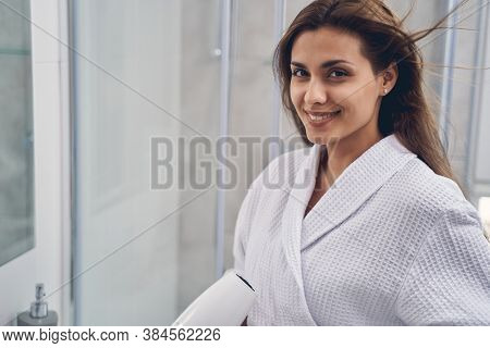 Charming Young Woman Styling Hair With Hair Dryer