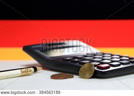 Ten Germany Euro Cent On Reverse And Two Coin Of Two Euro Cent On White Floor With Black Calculator