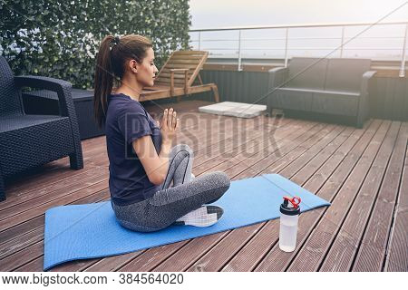 Serene Young Woman Practicing Yoga On Rooftop Terrace