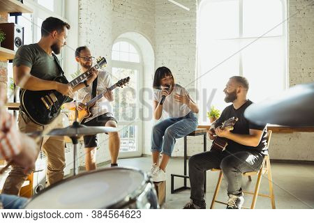 Inspiration. Musician Band Jamming Together In Art Workplace With Instruments. Caucasian Men And Wom