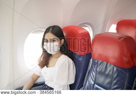 A Travelling Woman Is Wearing Protective Mask Onboard In The Aircraft, Travel Under Covid-19 Pandemi