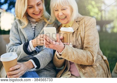 Happy Smiling Two Adult Ladies Looking At The Screen Mobile Phone