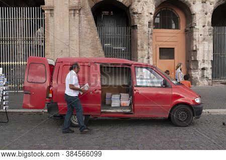 Rome, Italy - June 27, 2010: A Man Collects Maps And Guides In A Red Van, Which He Has For Sale, Fro