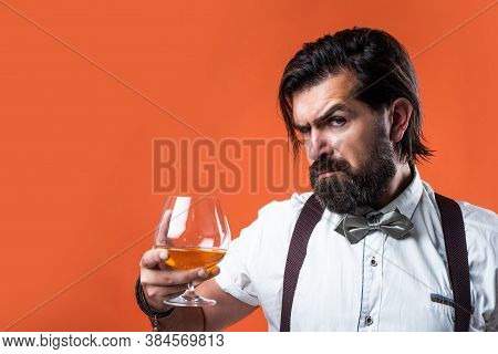 Retro Man In Bow Tie Relaxing With Alcohol. Confident Elegant Bartender In Classical Wear Drinking B