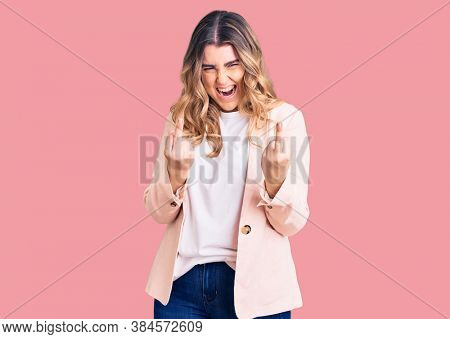 Young caucasian woman wearing business clothes showing middle finger doing fuck you bad expression, provocation and rude attitude. screaming excited