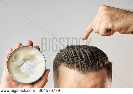 Man Applying A Clay, Pomade, Wax, Gel Or Mousse From Round Metal Box For Styling His Hair After Barb