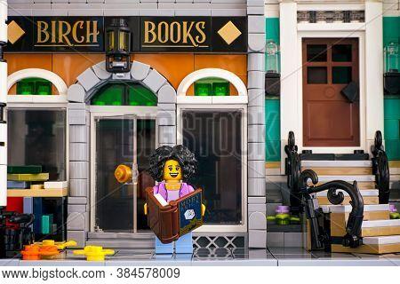 Tambov, Russian Federation - June 26, 2020 Lego Woman Minifigure With Book Stands Near Birch Books B