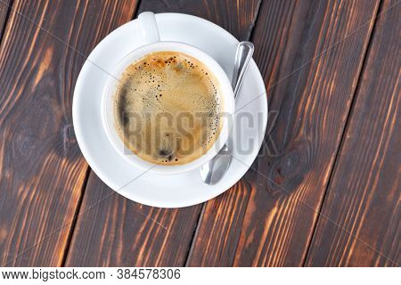 cup of coffee on the wooden background
