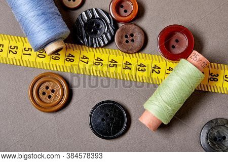 Background and texture of multicolored antique buttons and sewing tools