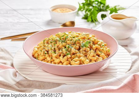 Vegan Mac And Cheese With Nutritional Yeast Sauce In A Pink Bowl On A White Wooden Table With Golden
