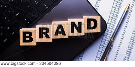 The Word Brand Is Written On Wooden Cubes Near The Pen And Documents. Marketing Concept