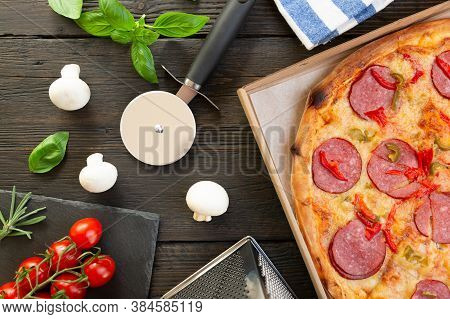 Tasty Hot Pizza With Ingredients And Pizza Cutting Knife On A Black Texture Background Top View