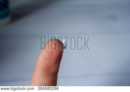 Contact Lenses Macro Close Up. Man Holding Lens On Finger.